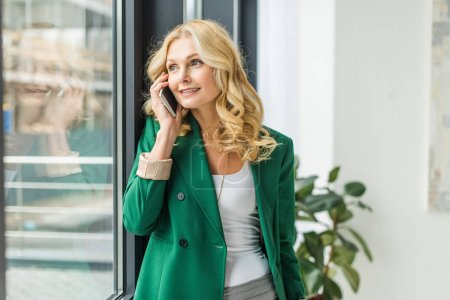 Photo for Smiling businesswoman talking by smartphone and looking at window - Royalty Free Image