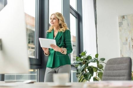 selective focus of smiling middle aged businesswoman holding digital tablet and looking away at workplace