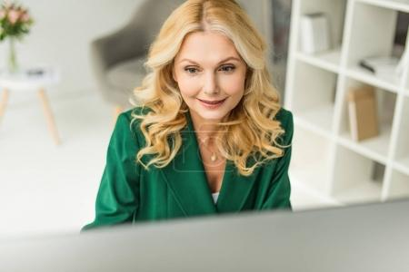 high angle view of smiling businesswoman working with desktop computer in office