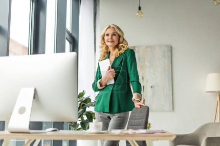 Photo for Smiling middle aged businesswoman holding digital tablet at workplace - Royalty Free Image