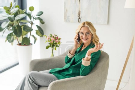 high angle view of smiling middle aged businesswoman in eyeglasses talking by smartphone