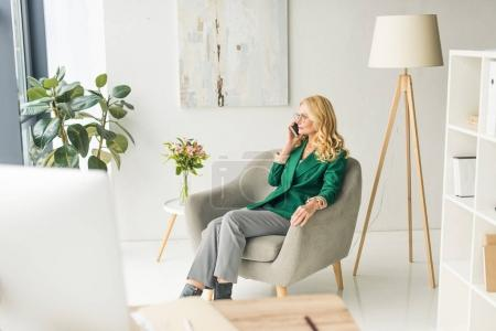 Photo for High angle view of middle aged businesswoman talking by smartphone in office - Royalty Free Image