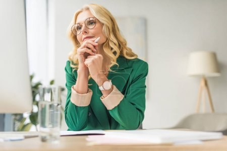 Photo for Mature businesswoman in eyeglasses holding pen and using desktop computer at workplace - Royalty Free Image