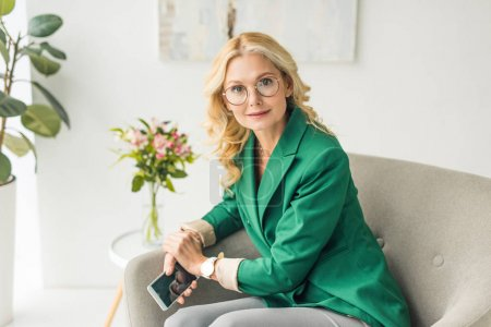 mature businesswoman in eyeglasses holding smartphone and looking at camera