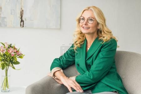Photo for Beautiful mature businesswoman smiling and looking away while sitting in armchair - Royalty Free Image