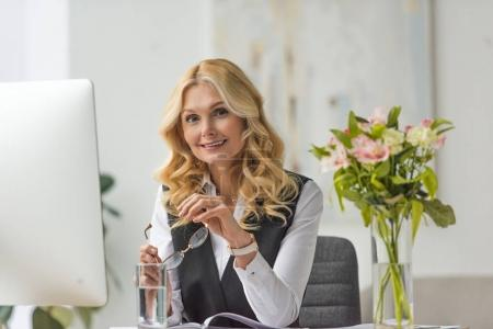 beautiful businesswoman holding eyeglasses and smiling at camera