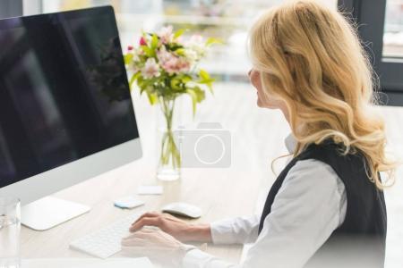 attractive mature businesswoman using desktop computer at workplace