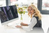 businesswoman using desktop computer and looking at camera at workplace