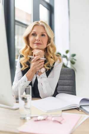 smiling middle aged businesswoman working with papers and desktop computer