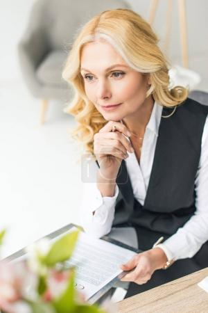 smiling focused businesswoman holding pen with contract and looking away in office