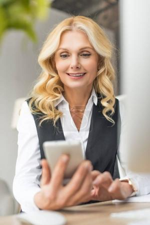 selective focus of smiling middle aged businesswoman using smartphone