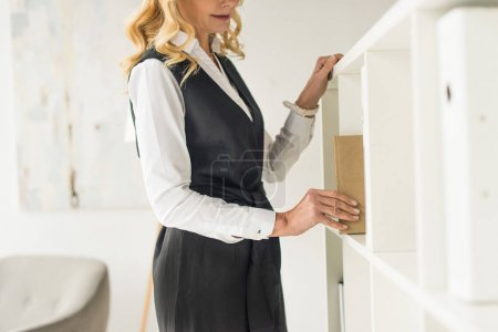 cropped shot of businesswoman taking book from shelf
