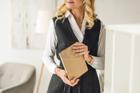 cropped shot of smiling businesswoman holding book