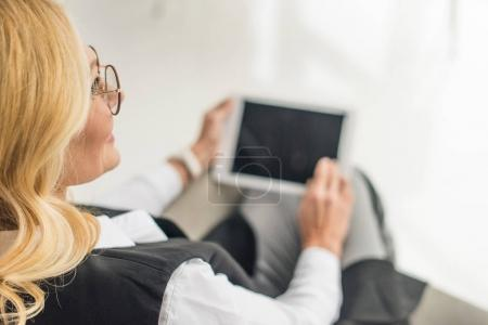 cropped shot of businesswoman in eyeglasses using digital tablet with blank screen