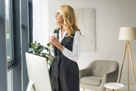 pensive businesswoman holding cup of coffee and looking at window