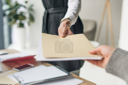 cropped shot of businesswoman giving envelope to colleague at workplace