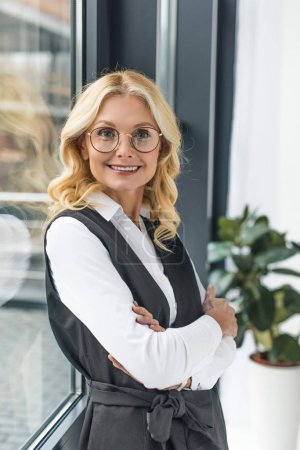 portrait of beautiful middle aged businesswoman with crossed arms smiling at camera