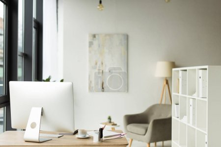modern office interior with desktop computer and papers on table