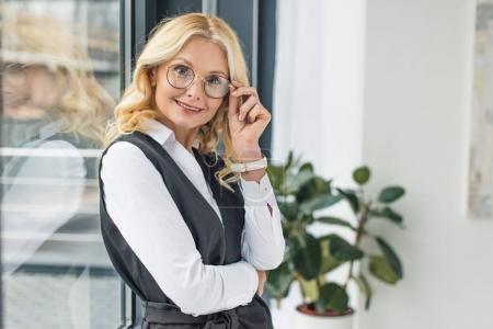 portrait of beautful mid adult businesswoman in eyeglasses smiling at camera