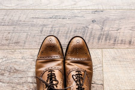 top view of pair of leather brown shoes on wooden floor