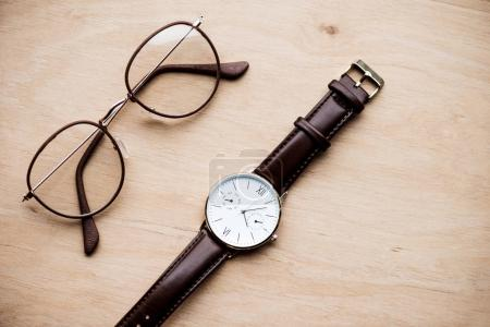 top view of glasses and watch on wooden surface