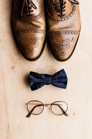 top view of shoes, tie bow and glasses on wooden floor