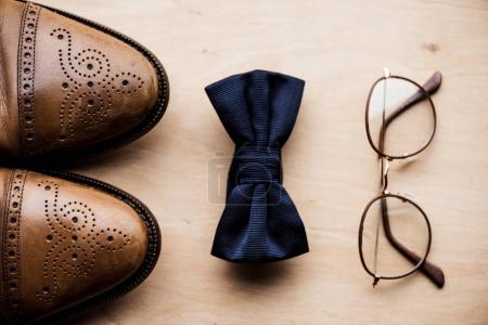 top view of shoes, tie bow and glasses on wooden surface