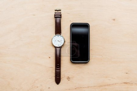 top view of watch and turned off smartphone on wooden table