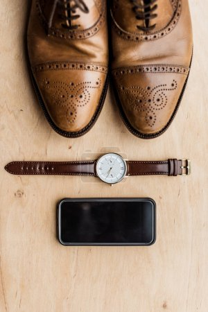 Photo for Top view of shoes, smartphone and watch on wooden surface - Royalty Free Image