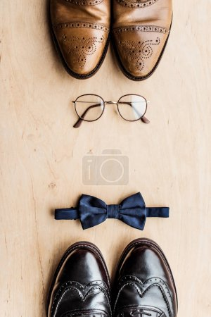 top view of shoes, glasses and tie bow on wooden surface