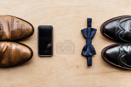 top view of shoes, smartphone and tie bow on wooden surface