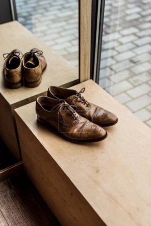 high angle view of modern brown male shoes at showcase in shop