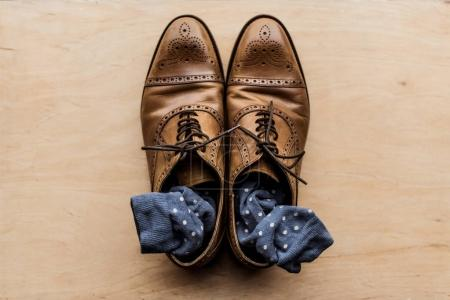 top view of brown male shoes with socks inside