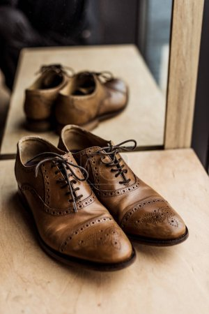 modern brown male shoes at showcase in shop