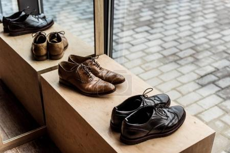modern brown and black male shoes at showcase in shop