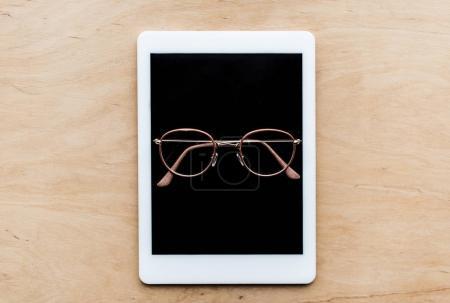 Foto de Vista superior de vidrios en tableta en mesa de madera - Imagen libre de derechos