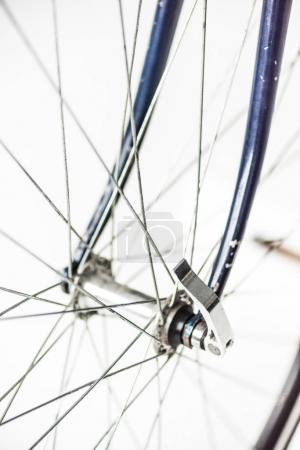 close up of bicycle wheel with spokes and fork isolated on white