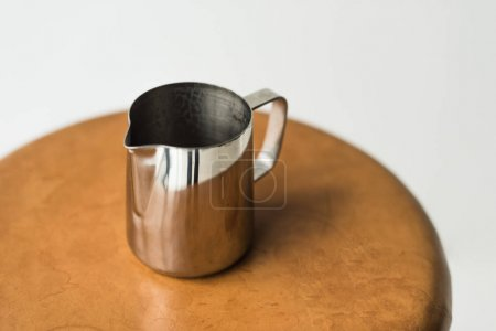 high angle view of stainless milk pitcher on wooden chair isolated on white