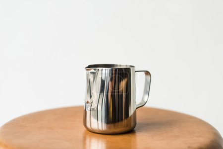 stainless milk pitcher on wooden chair isolated on white