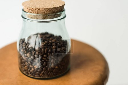 glass bottle with coffee beans and cap on table isolated on white