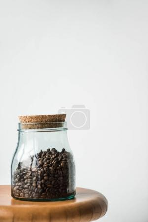 glass bottle with coffee beans and cap on wooden stand isolated on white
