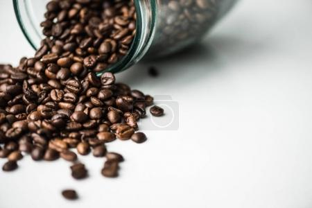 scattered coffee beans from glass bottle on white