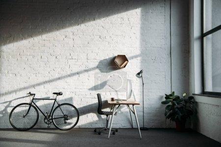 Foto de Bicicletas y mesa de trabajo con la computadora en la oficina - Imagen libre de derechos