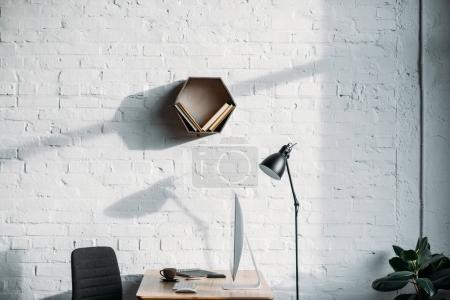 Photo pour Lampe de table, ordinateur et étagère sur le mur dans le bureau - image libre de droit