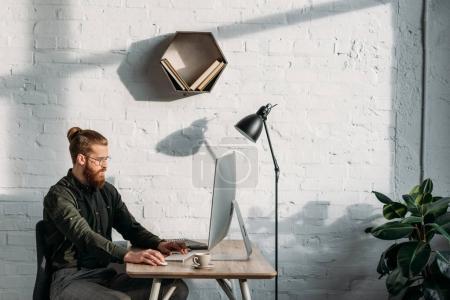 Photo pour Vue de côté du bel homme d'affaires travaillant avec l'ordinateur dans le bureau - image libre de droit