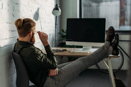 side view of businessman sitting with legs on office table
