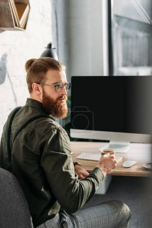 bearded businessman holding cup of coffee in office