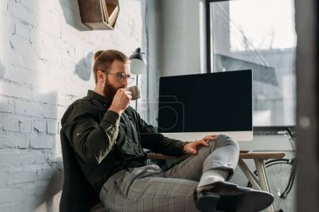 handsome businessman drinking coffee in office