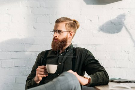 handsome businessman holding cup of coffee and looking away