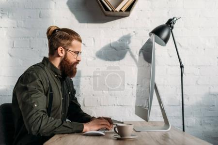 side view of handsome businessman using computer in office